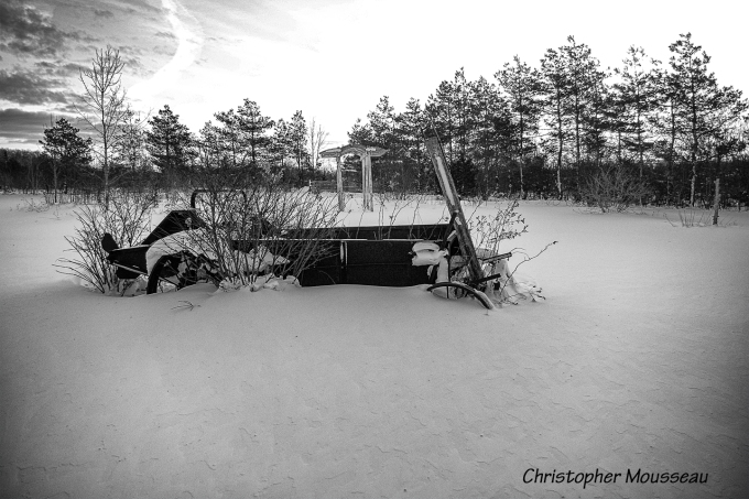 black and white photo of an antique Massey Ferguson manure spreader, abandoned in a snow covered field.