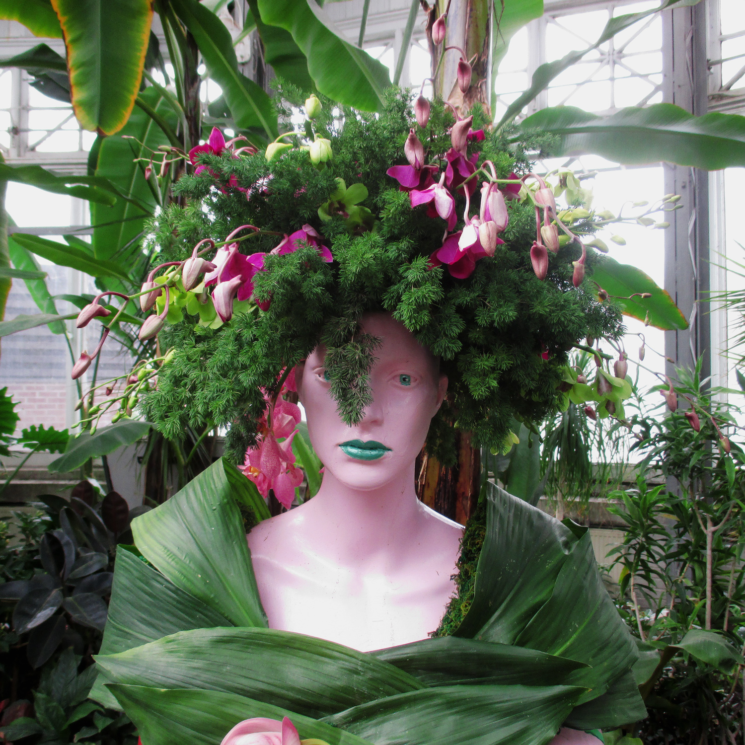 close up of mannequin decorated with plants, foliage and orchids