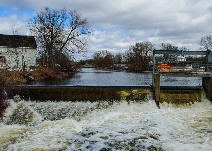 Melting snow during winter's final days leads to a huge water flow over the low Consecon mill dam.  Cloudy skies, with blue peeking out here and there.