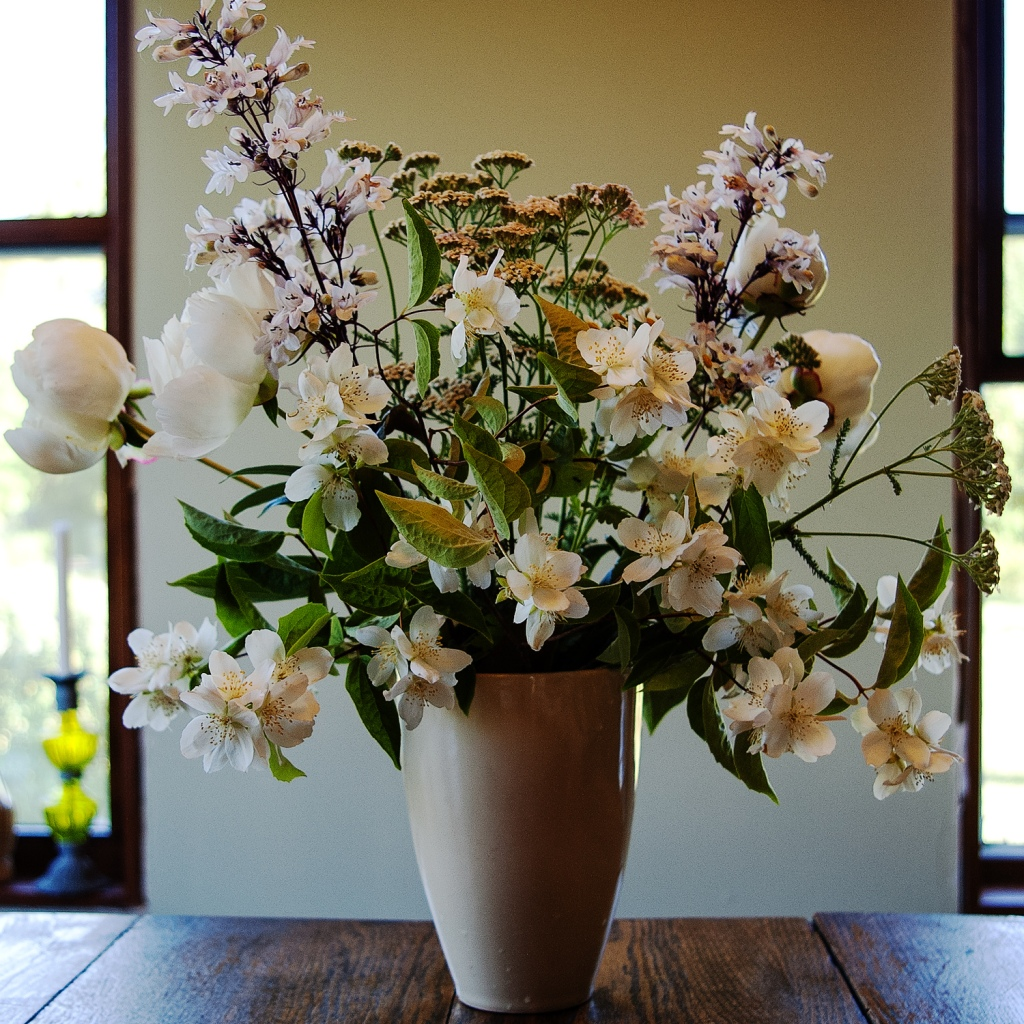 White porcelain vase filled with white flowers.